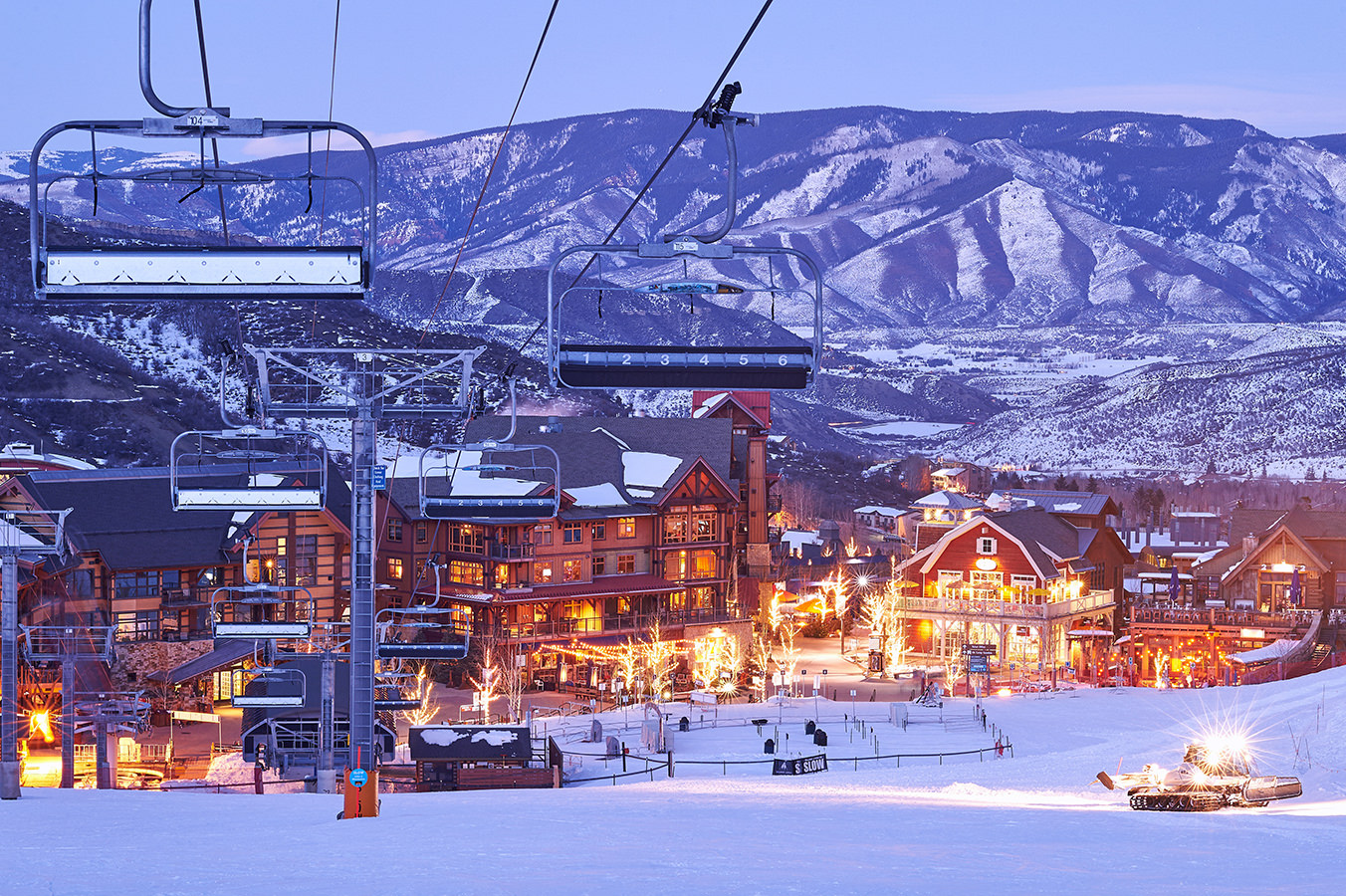 Dusk photography of Snowmass Village with a snowcat in winter